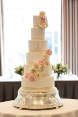 pink and ivory roses on large white cake with light gold details at the berkeley