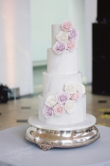 pink and lilac roses on large marble wedding cake at kew gardens