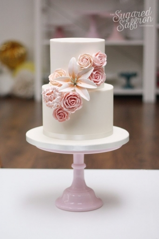 peach roses and lily i centre of two tier white wedding cake