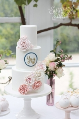 small white wedding cake with pink roses and monogram