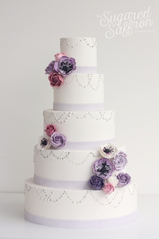 large white cake with pearl piping and purple sugar flowers