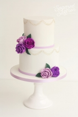 white cake with gold piped swags and purple roses