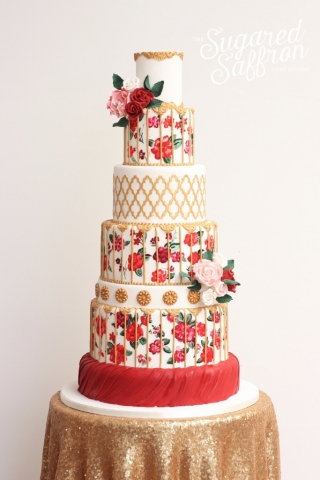 handpainted red flowers on white cake with gold details and sugar flowers