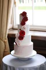 red and pink roses on white cake with pink marble
