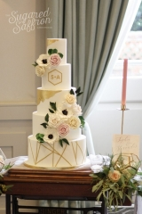 sugar anemones and roses cascading down a white cake with gold leaf details and geometric base