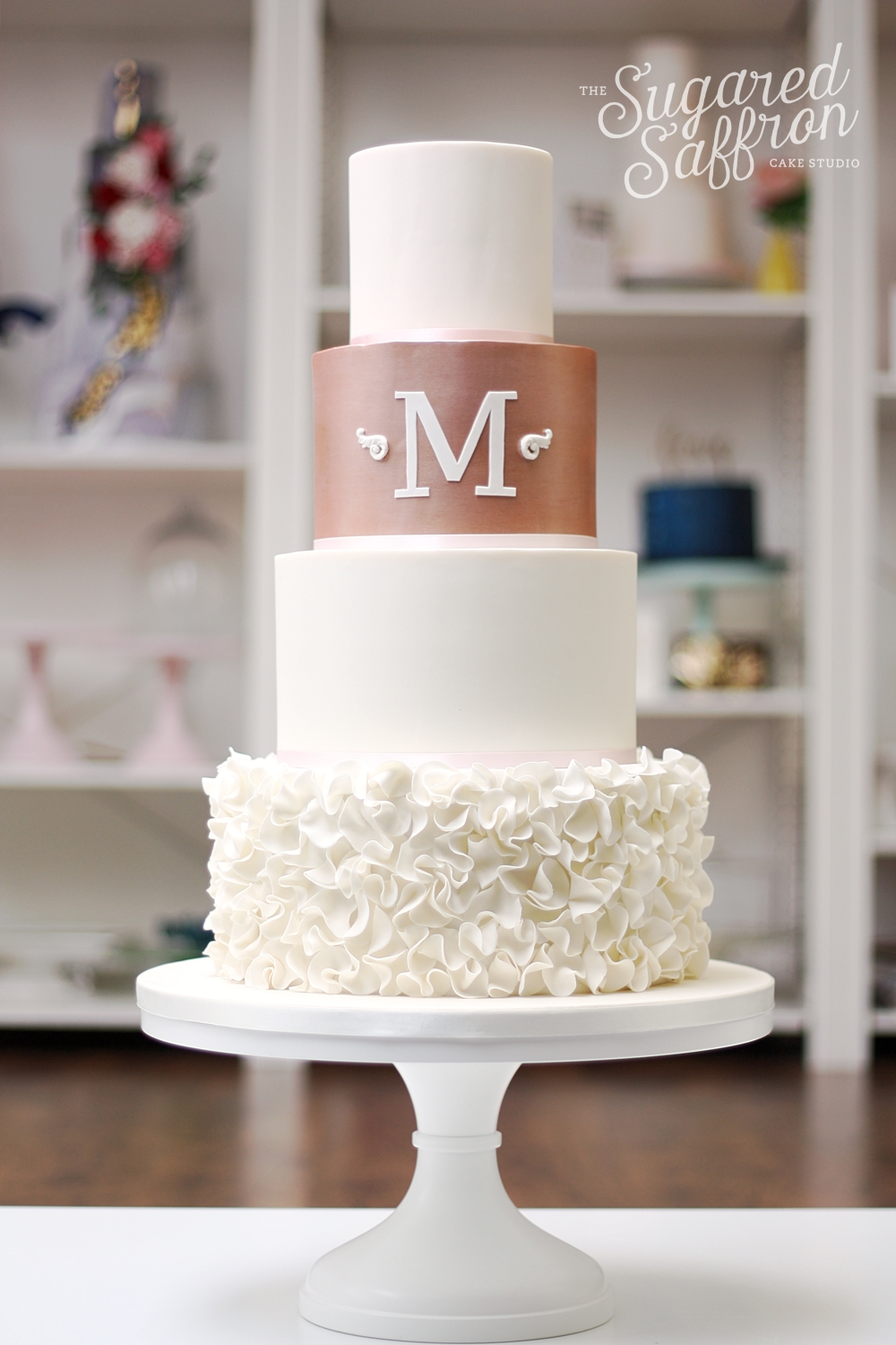 ivory wedding cake with ruffles and rose gold tier and monogram