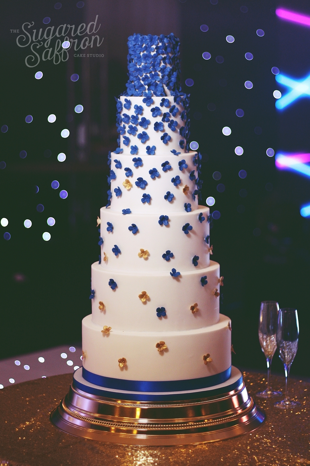 royal blue hydrangeas falling from white wedding cake with gold