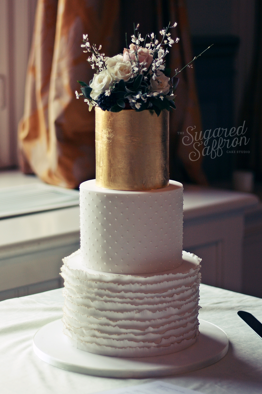 Ruffles, Dots and Gold wedding cake with fresh foliage topper