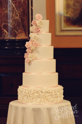 large wedding cake with ruffled bottom tier. cascade of sugar roses in white and pink