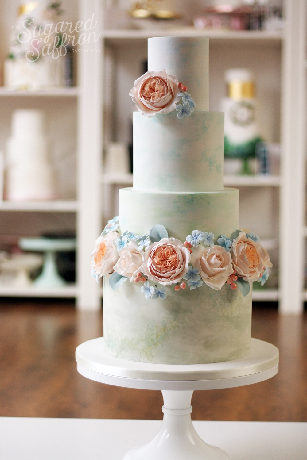 sage green and blue watercolour wedding cake with peach david austin roses