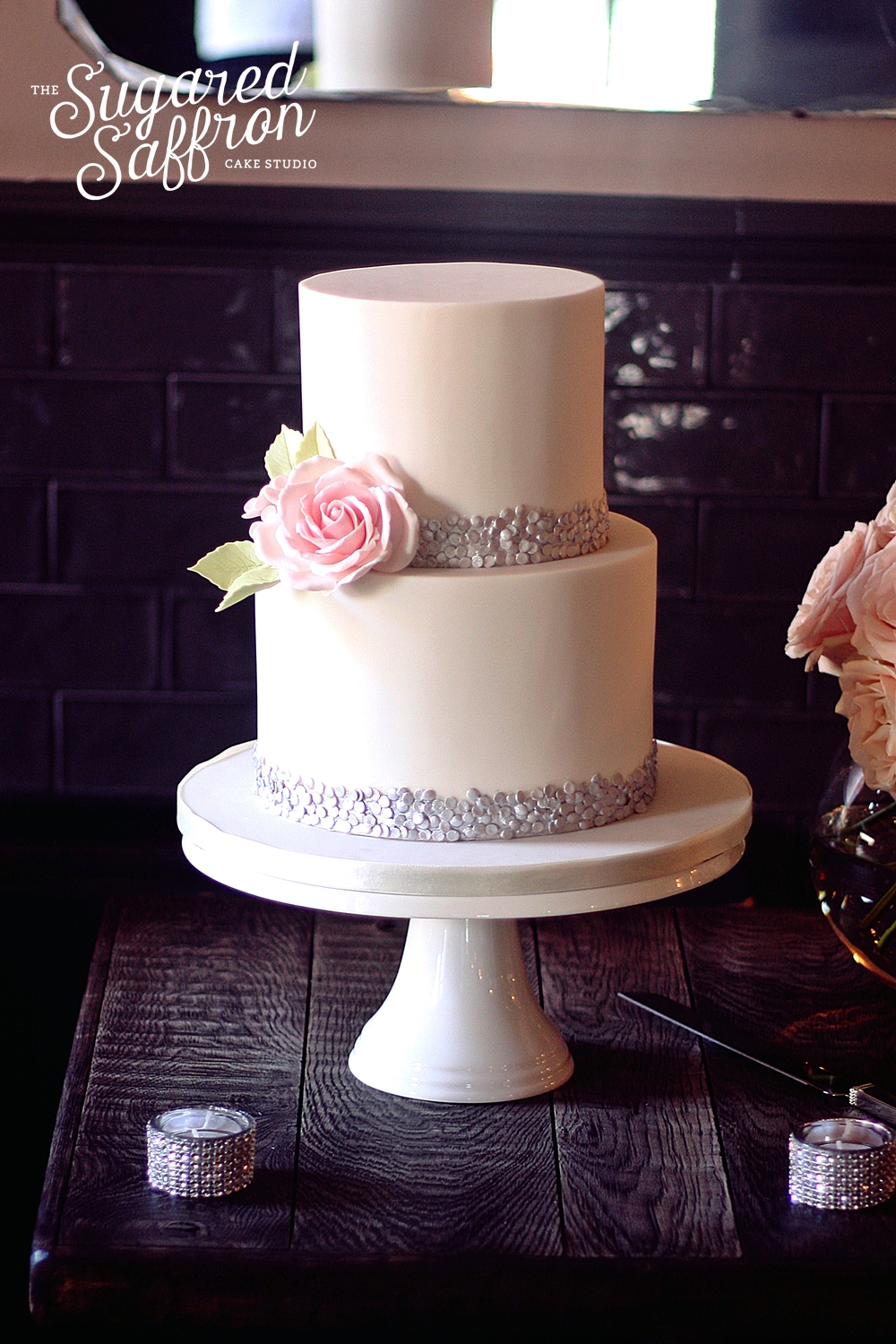 white wedding cake with silver sequin border and pink rose