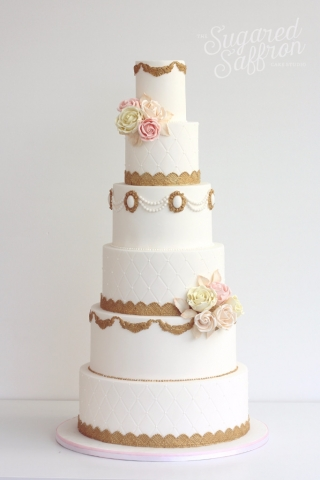 tall white cake with dark gold details