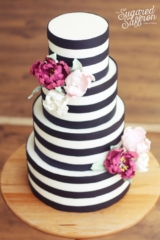 Black and white striped wedding cake with pink peonies