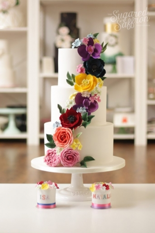 white wedding cake with brightly coloured sugar flowers cascading