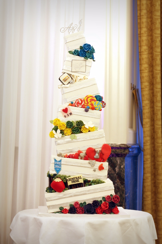 Topsy turvy wedding cake in bright colours with silver leaf stripes
