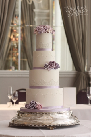 white cake with lilac ribbon and roses and edible lace