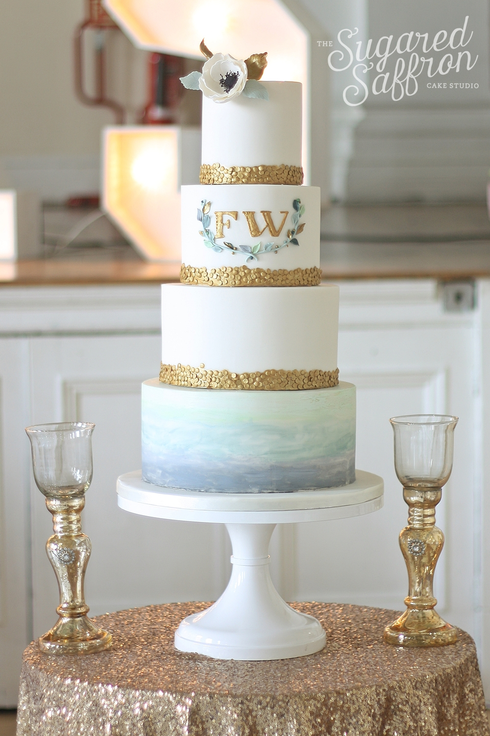 Watercolour green and blue wedding cake with gold sequins and monogram wreath