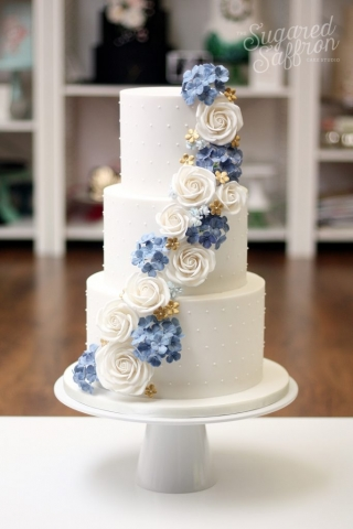 white roses and blue hydrangea on white wedding cake