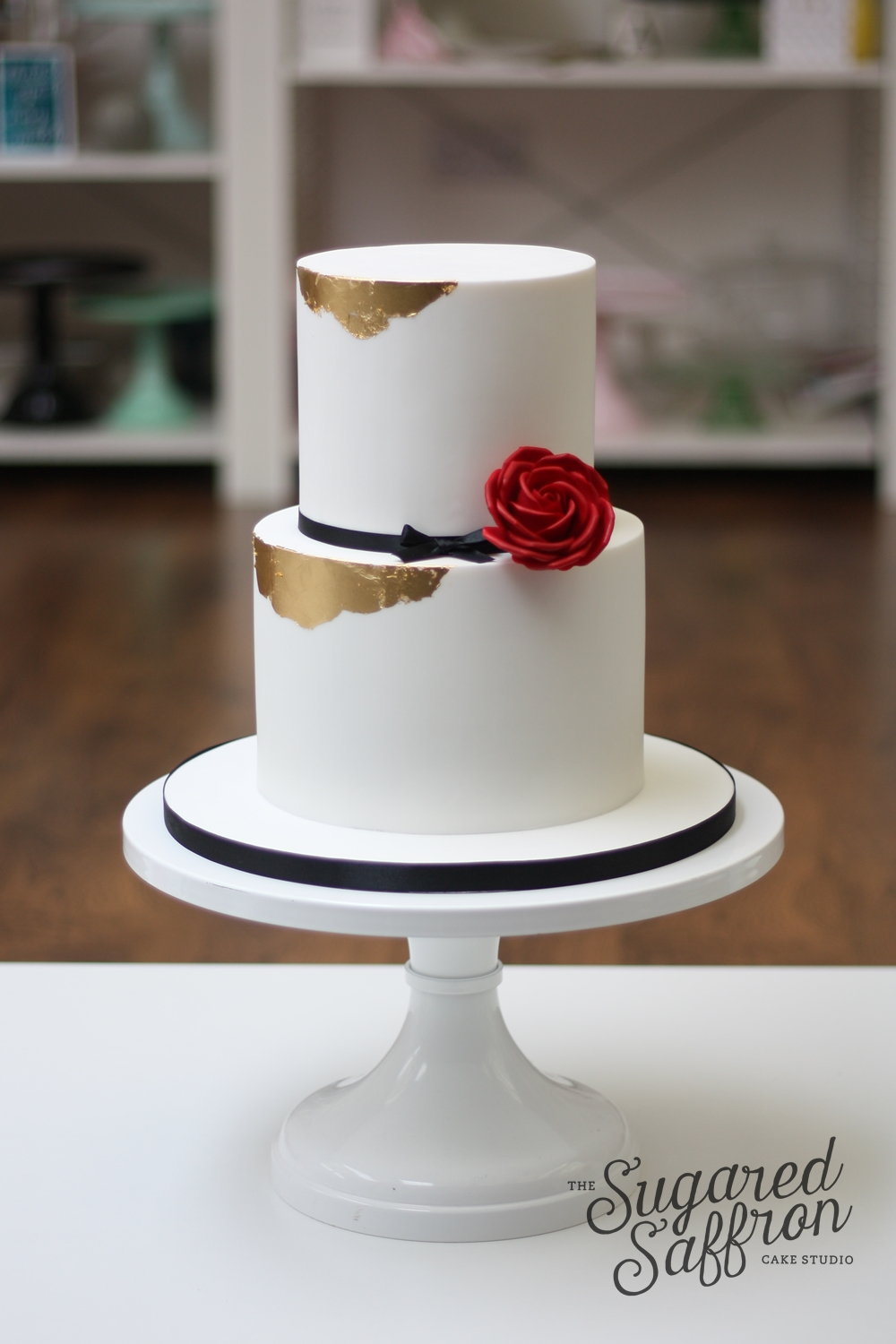 White cake with gold leaf edges and single red rose