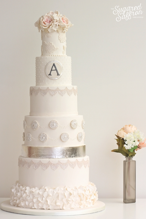 White and silver leaf wedding cake with monogram and pink roses