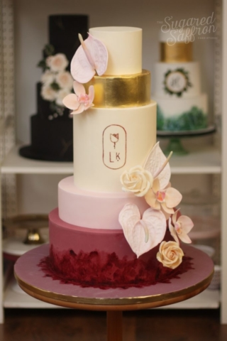 Ivory base with scarlet bottom tier and pink and gold. Sugar Anthhurium and orchids as decoration.