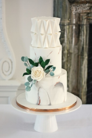 White and grey marble wedding cake with folded architectural design. White sugar rose and eucalyptus leaves.