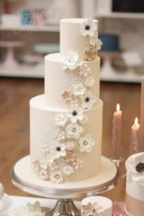 Nude wedding cake with asymmetrical tiers. Sugar flowers in white, brown, cream and nude colours.