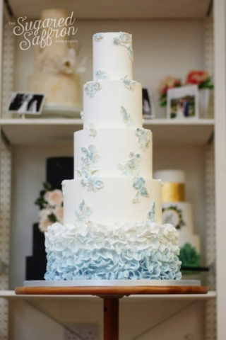 Ombre Blue ruffles on bottom tier, bas relief flowers and foliage on top tiers.
