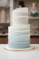 Graduated blue layer wedding cake with gold tips. Straight contemporary lines in ombre colour.