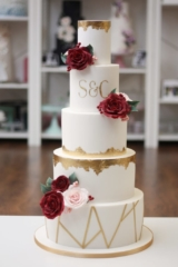 White cake with gold leaf edging. Burgundy sugar roses with blush roses and monogram