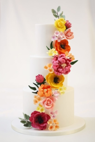 Sugar flower cascade wedding cake in bright yellow, orange and pink