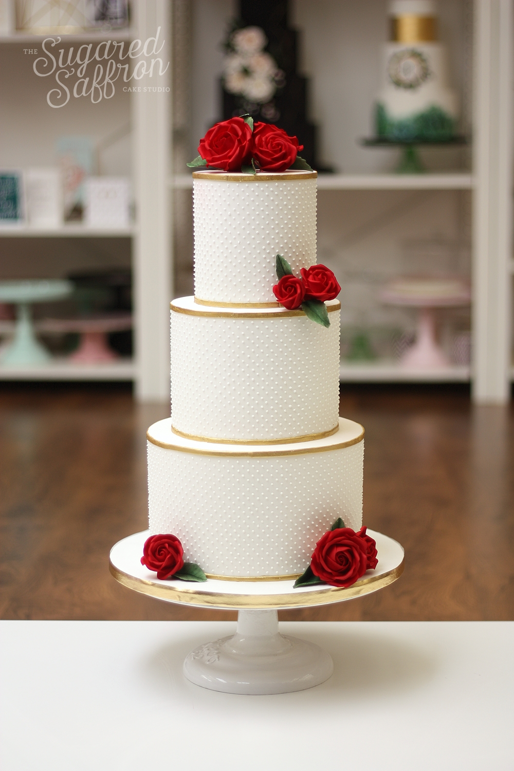 White cake with swiss dots and red roses in london