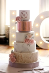 Marble wedding cake with copper leaf and copper monogram. Peach and pink sugar roses with grey green leaves and Stoke School.