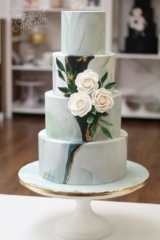 Emerald green marble wedding cake with foliage ruscus and white sugar roses in london studio