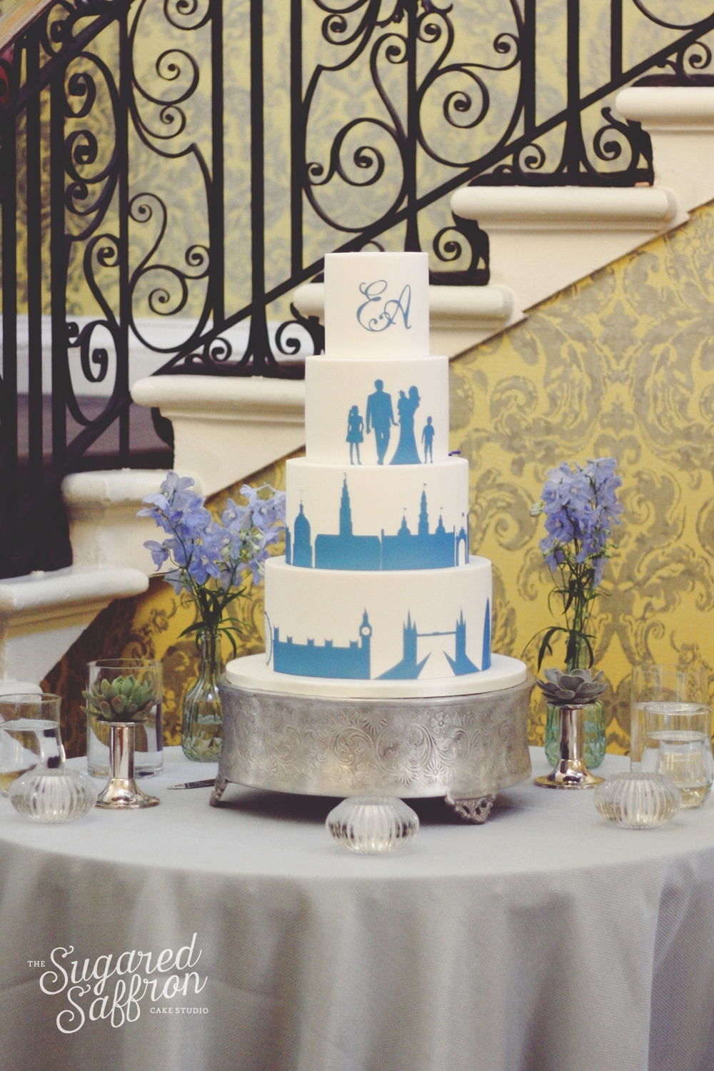 Blue silhouette of family with London and Copenhagen skyline. Blue theme wedding cake at Hedsor House