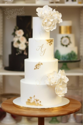 White wedding cake with gold leaf patches. Gold leaf initials and white sugar flowers for a wedding in London.