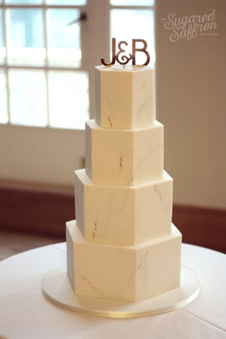Light grey marble hexagon wedding cake. Gold initial topper.