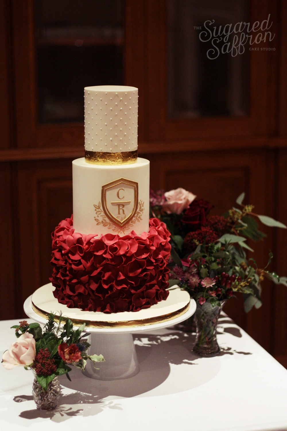 Ivory cake with burgundy wine red ombre ruffled. Gold leaf monogram and dots at the Ned London