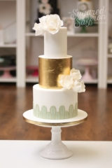 White and gold leaf cake with oversized roses and art deco design in mint green