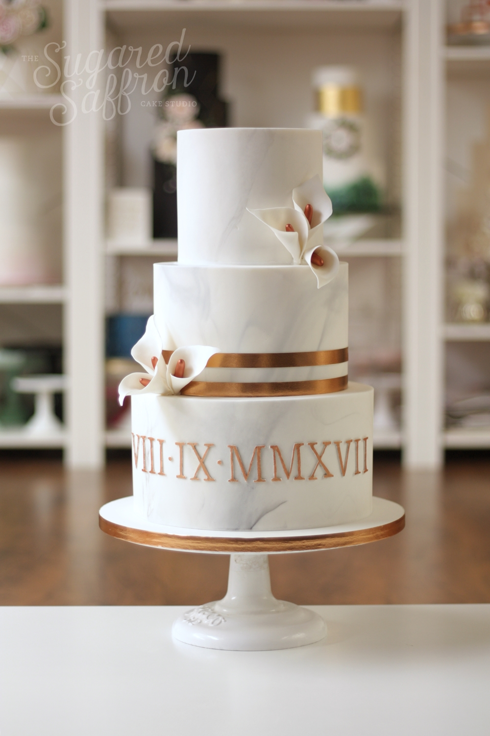 Marble wedding cake with copper stripes and roman numerals