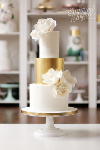 White wedding cake with edible gold leaf tier. Large white sugar flowers.