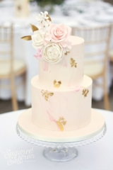 A pink marbled wedding cake with patches of gold leaf. Sugar roses in pink with gold leaves at Syon Park.