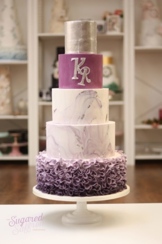 Purple marble and purple ombre ruffle bottom tier. Silver leaf top tier and initials.