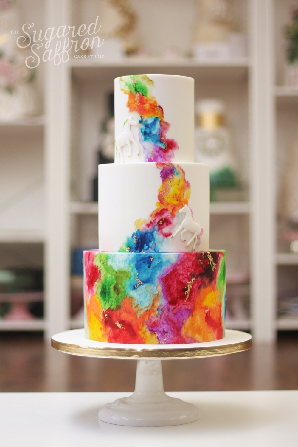 Watercolour rainbow wedding cake with unicorns