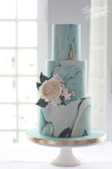 Teal green and blue marble wedding cake with david austin rose and flowers. Gold leaf through marble and dark green leaves.