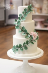 White wedding cake with sugar eucalpytus leaves. Diagonal cascading leaves with pink sugar rose and was flowers.