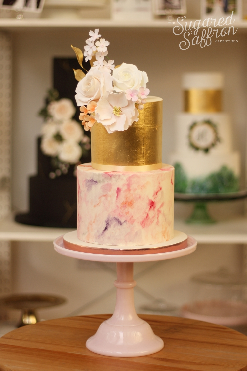 Gold leaf top tier with bottom tier in painted watercolour. Sugar flowers in white and pink on top.