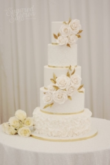 White wedding cake with damask stencil. Large white roses with gold leaves for London wedding