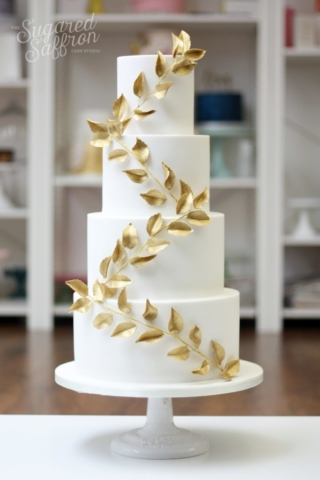 white wedding cake with wrapped gold sugar leaves