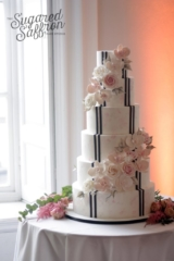 Pink flower watercolour wedding cake with modern black lines and pink roses and orchids